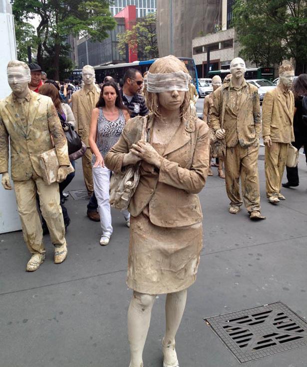 Com 5 kg de argila sobre o corpo, grupo caminha pela Av. Paulista