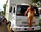 Mulher nua sobe em para-choque de caminhão e para o trânsito